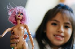 Śliczna mała dziewczynka bawić się z zabawkarską lalą zdjęcie royalty free