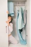 Śliczna mała dziewczynka chuje w garderobie Zdjęcie Stock