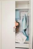 Śliczna mała dziewczynka chuje w garderobie Obrazy Stock