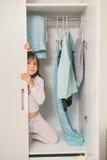 Śliczna mała dziewczynka chuje w garderobie Fotografia Stock
