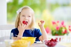 Śliczna mała dziewczynka cieszy się jej śniadanie w domu Ładny dziecko je i pije mleko przed szkołą kukurydzanych płatki i malink Fotografia Stock