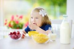Śliczna mała dziewczynka cieszy się jej śniadanie w domu Ładny dziecko je i pije mleko przed szkołą kukurydzanych płatki i malink Zdjęcie Stock