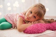 Śliczna mała dziewczynka cieszy się kłamać na podłoga w domu Wakacyjny li Obrazy Royalty Free