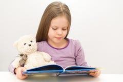 Śliczna mała dziewczynka czyta książkę Zdjęcie Stock