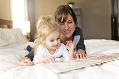 Śliczna mała dziewczynka czyta książkę z jej matką w sypialni obrazy royalty free