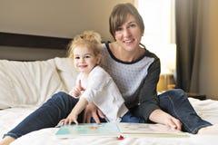Śliczna mała dziewczynka czyta książkę z jej matką w sypialni zdjęcie stock