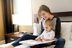 Śliczna mała dziewczynka czyta książkę z jej matką w sypialni obraz stock
