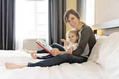 Śliczna mała dziewczynka czyta książkę z jej matką w sypialni obrazy stock