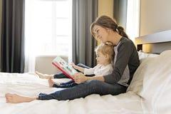 Śliczna mała dziewczynka czyta książkę z jej matką w sypialni obraz royalty free
