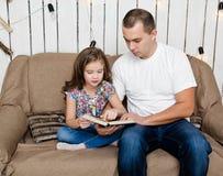Śliczna mała dziewczynka czyta książkę z jej ojcem na kanapie Obrazy Royalty Free