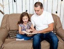 Śliczna mała dziewczynka czyta książkę z jej ojcem na kanapie Obraz Royalty Free