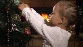 Śliczna mała dziewczynka dekoruje choinki w ciemnym pokoju z grabą zdjęcie wideo