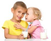 Śliczna mała dziewczynka i chłopiec pijemy mleko Zdjęcie Royalty Free