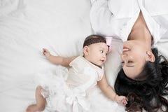 Śliczna mała dziewczynka i jej macierzysty lying on the beach na podłodze zdjęcia stock