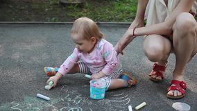 Śliczna mała dziewczynka i jej macierzysty rysunek z kredą na chodniczku przy lato parkiem Rodzina, macierzyństwo i ludzie pojęć, zbiory