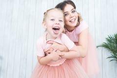 Śliczna mała dziewczynka i jej mama bawić się obok rośliien w garnkach na białym tle obraz stock
