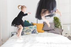 Śliczna mała dziewczynka i jej mama zabawę na łóżku w domu zdjęcie stock