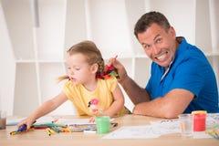Śliczna mała dziewczynka i jej ojciec maluje wpólnie Obrazy Royalty Free