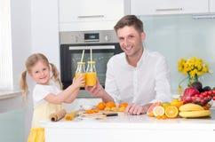 Śliczna mała dziewczynka i jej tata pije sok zdjęcie royalty free