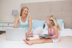 Śliczna mała dziewczynka i matka na łóżkowej używa pastylce i laptopie Obraz Royalty Free
