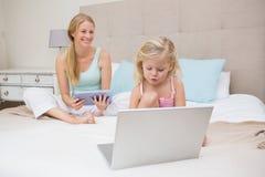 Śliczna mała dziewczynka i matka na łóżkowej używa pastylce i laptopie Fotografia Royalty Free