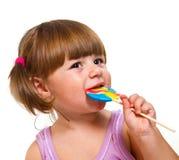 Śliczna mała dziewczynka je barwionego lizaka Zdjęcia Royalty Free