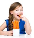 Śliczna mała dziewczynka je marchewki Fotografia Royalty Free