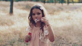 Śliczna mała dziewczynka jest dmuchać mydlani bąble zbiory