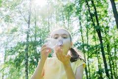 Śliczna mała dziewczynka jest dmuchać mydlani bąble fotografia royalty free