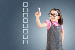 Śliczna mała dziewczynka jest ubranym biznes suknię i pisze na niektóre pustej liście kontrolnej boksuje niebieska tła obraz stock