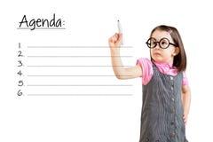Śliczna mała dziewczynka jest ubranym biznes suknię i pisze pustym agendy listy bielu tle Fotografia Stock