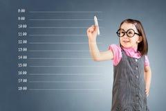 Śliczna mała dziewczynka jest ubranym biznes suknię i pisze pustym nominacyjnym rozkładzie niebieska tła Obraz Royalty Free