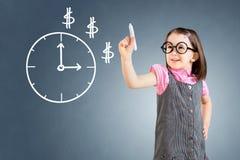 Śliczna mała dziewczynka jest ubranym biznesu rysunek i suknię czas na whiteboard niebieska tła Obraz Stock