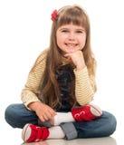 Śliczna mała dziewczynka jest ubranym cajgu całkowitego obsiadanie na podłoga i Zdjęcie Royalty Free