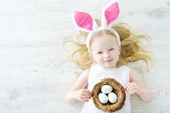 Śliczna mała dziewczynka jest ubranym królików ucho bawić się jajecznego polowanie na wielkanocy Fotografia Stock