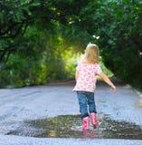 Śliczna mała dziewczynka jest ubranym podeszczowych buty Obrazy Stock