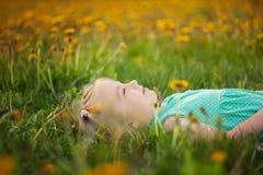 Śliczna mała dziewczynka kłama na trawie w kwiat polanie w lecie zdjęcie stock