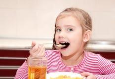 Śliczna mała dziewczynka ma śniadaniowych zboża z mlekiem Zdjęcie Stock
