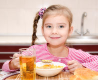 Śliczna mała dziewczynka ma śniadaniowych zboża z mlekiem Zdjęcia Stock