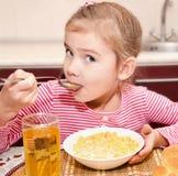Śliczna mała dziewczynka ma śniadaniowych zboża z mlekiem i sokiem Obrazy Stock