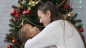 Śliczna mała dziewczynka ma zabawę i całuje jej mamy obok choinki zbiory