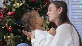Śliczna mała dziewczynka ma zabawę i całuje jej mamy obok choinki zdjęcie wideo