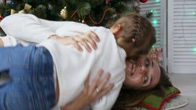 Śliczna mała dziewczynka ma zabawę i całuje jej mamy obok choinki zbiory wideo