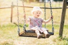 Śliczna mała dziewczynka ma zabawę na huśtawce obrazy royalty free