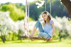 Śliczna mała dziewczynka ma zabawę na huśtawce w kwitnąć starego jabłoń ogród outdoors na pogodnym wiosna dniu obrazy stock