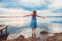 Śliczna mała dziewczynka ma zabawę na jeziorze Zdjęcia Royalty Free