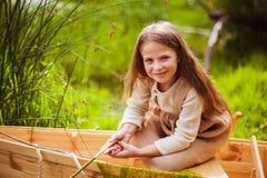 Śliczna mała dziewczynka ma zabawę w łodzi rzeką Zdjęcie Royalty Free