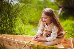 Śliczna mała dziewczynka ma zabawę w łodzi rzeką Obrazy Stock