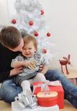 Śliczna mała dziewczynka ma zabawę z jej ojcem blisko bożych narodzeń Zdjęcie Stock