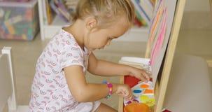 Śliczna mała dziewczynka miesza farby dla jej obrazu Obraz Stock